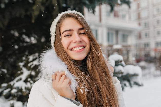 Retrato incrível mulher alegre com longos cabelos morenos na neve, aproveitando o inverno na rua. emoções brilhantes, ótimo humor, sorriso, felicidade, férias de inverno.