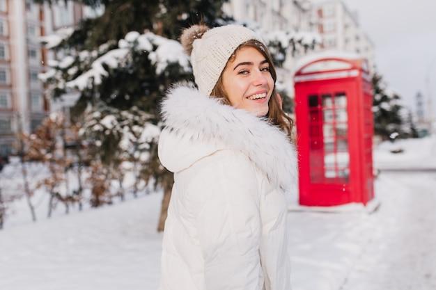 Retrato incrível sorridente jovem inverno andando na rua cheia de neve na manhã ensolarada. cabine telefônica vermelha, estilo britânico, aproveitando o frio