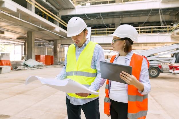 Retrato industrial de engenheiros e engenheiros na construção de prédio administrativo comercial