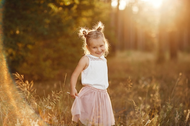 Retrato infantil de uma menina. menina bonita ao pôr do sol