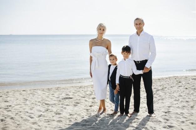 Retrato informal de família na praia de areia no dia ensolarado de verão, de pais e dois filhos vestidos em trajes formais