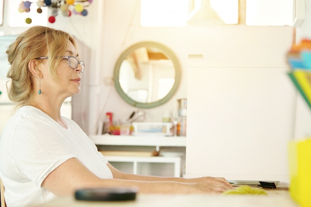 Retrato interior da atraente avó loira moderna assistindo suas séries de tv favoritas no computador pessoal, sentado com as costas retas e descansando as mãos na mesa, parecendo interessado e focado