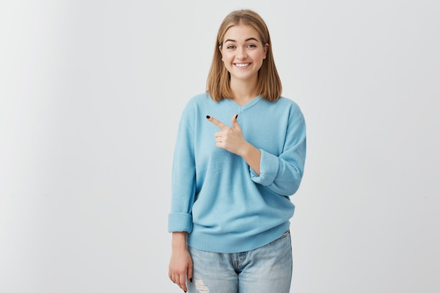 Retrato interior da bela jovem bonita com cabelo loiro, vestindo jeans e suéter azul casual com sorriso agradável, apontando com o dedo no espaço da cópia para a sua propaganda ou texto.