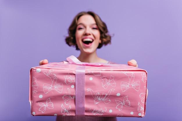 Retrato interior da feliz garota de cabelos curtos com caixa de presente rosa em primeiro plano. desfoque a foto de uma mulher morena sorridente na parede roxa com o presente de natal em foco.