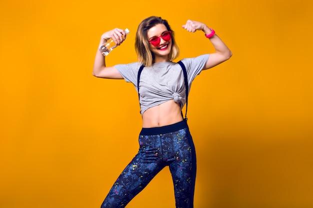 Retrato interior da menina da risada brincando com os músculos em fundo amarelo. mulher jovem bem torneada em legging e camiseta cinza, segurando uma garrafa de água e fazendo esportes.