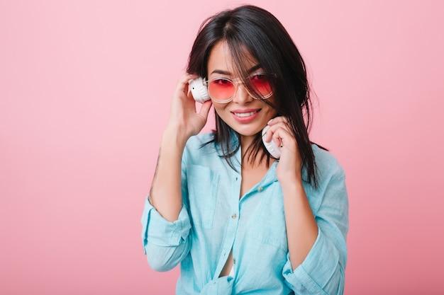 Retrato interior da tímida garota latina em óculos de sol rosa, ouvindo música em grandes fones de ouvido brancos. romântica senhora asiática de cabelos negros na camisa de algodão azul, curtindo a música favorita.