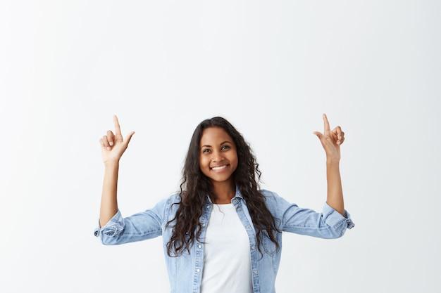 Retrato interior de alegre alegre garota afro-americana vestida casualmente com cabelos longos ondulados, apontando os dedos para cima, indicando algo interessante, tendo um olhar animado feliz.