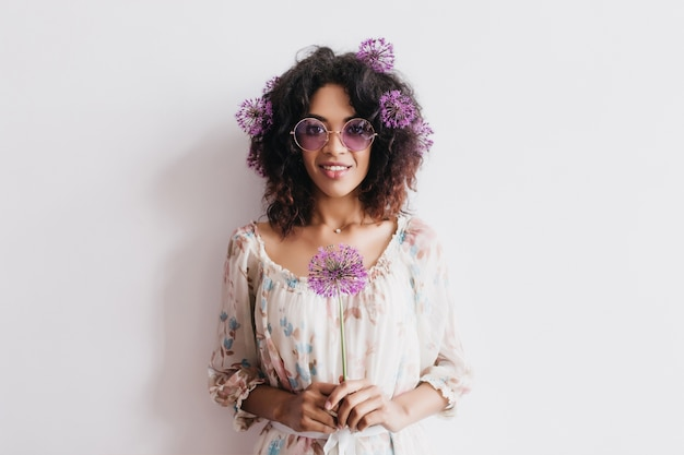 Retrato interior de atraente mulher negra com cabelo encaracolado, segurando allium. linda garota africana posando com flores roxas.