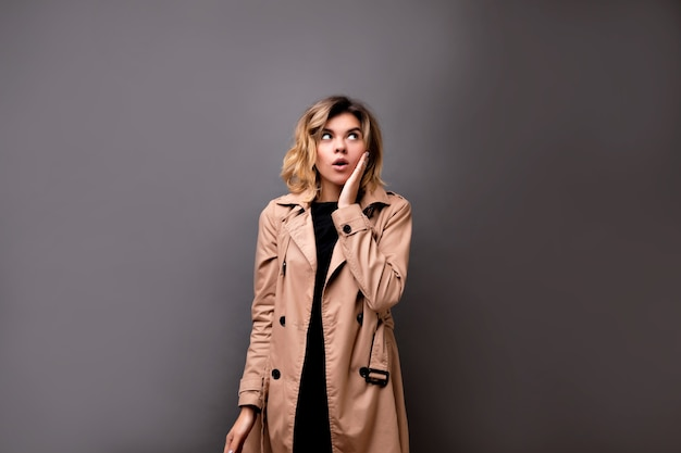 Retrato interior de close-up de menina adorável com cabelo curto loiro vestido bege casaco em pé sobre cinza isolado. graciosa jovem pálida com corte de cabelo curto