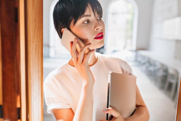 Retrato interior de close-up de mulher jovem ocupada com lábios vermelhos e penteado curto da moda falando ao telefone