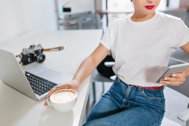 Retrato interior de close-up de uma menina sorridente de camisa branca, pausa para o café no escritório