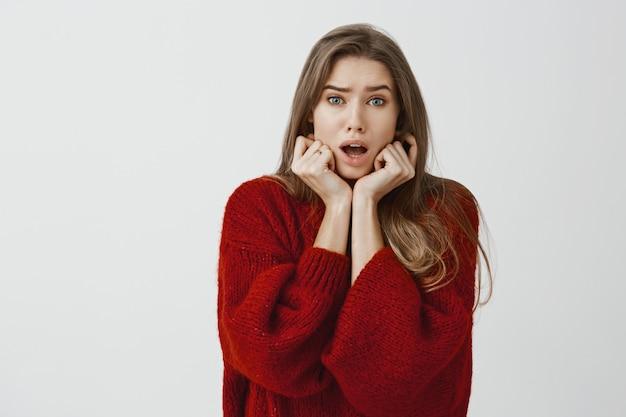 Retrato interior de colega de trabalho feminina europeia timit preocupada em suéter solto vermelho, de mãos dadas no queixo e mandíbula solta, sendo ansiosa e nervosa, amiga simpatizante no hospital ao longo da parede cinza