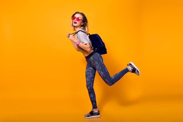 Retrato interior de corpo inteiro de menina vestindo leggings, correndo sobre fundo amarelo. modelo feminino muito magro em tênis com mochila brincando no estúdio.