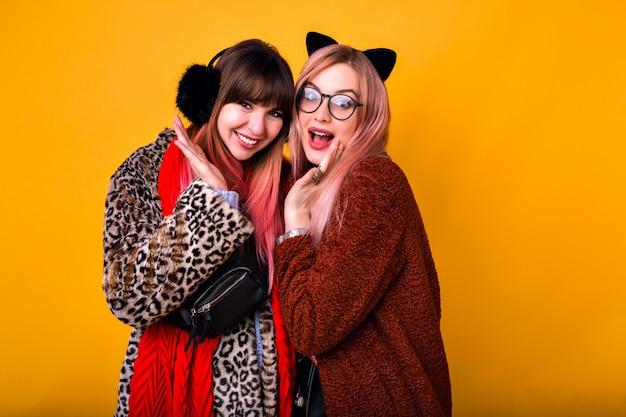 Retrato interior de duas lindas mulheres felizes sorrindo e se divertindo, vestindo casacos de pelúcia super da moda e orelhas quentes engraçadas, clima de inverno