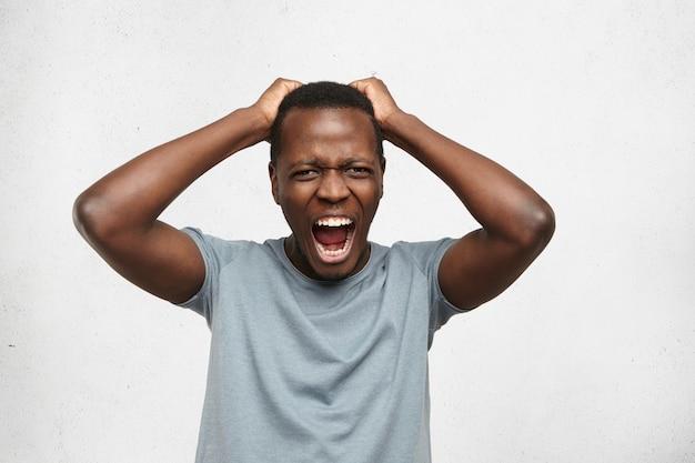 Retrato interior de homem afro-americano estressado, estressado, vestido com camiseta cinza, segurando as mãos na cabeça e gritando alto em desespero e raiva, furioso com o barulho vindo do apartamento acima dele