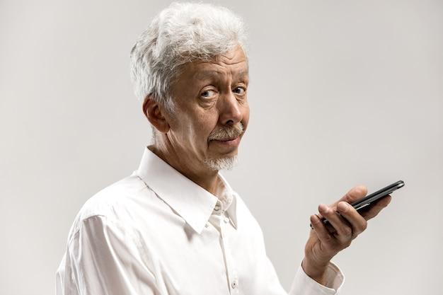 Retrato interior de homem atraente sênior isolado na parede cinza, segurando o smartphone em branco, usando controle de voz, sentindo-se feliz e surpreso. emoções humanas, conceito de expressão facial.