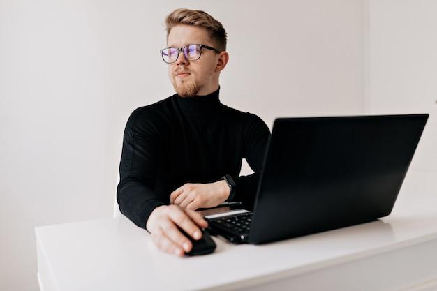 Retrato interior de homem loiro bonito, trabalhando no laptop no escritório moderno branco.