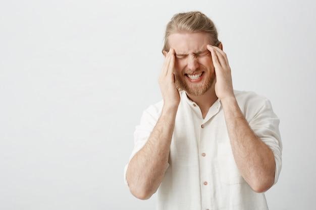 Retrato interior de homem loiro caucasiano com barba que sofre de enxaqueca ou dor de cabeça, segurando os dedos nos templos