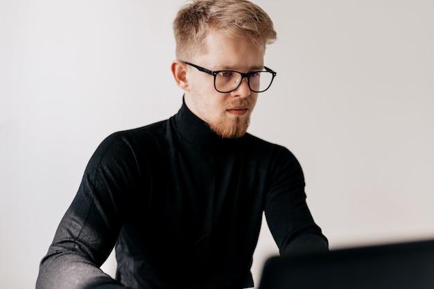 Retrato interior de jovem europeu vestindo pulôver preto e óculos trabalhando com laptop no escritório claro em dia ensolarado.