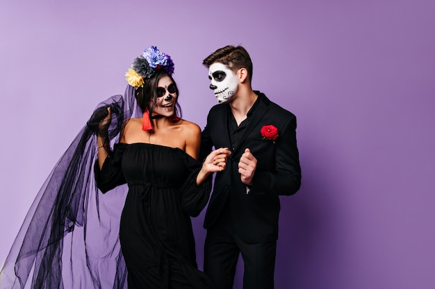 Retrato interior de jovem num vestido preto da noiva e do noivo com uma rosa no bolso dançando no fundo isolado.