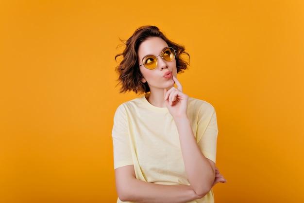 Retrato interior de menina morena pensativa em t-shirt amarelo claro. ainda bem que mulher de cabelos curtos em óculos de sol, olhando para cima e pensando em algo.