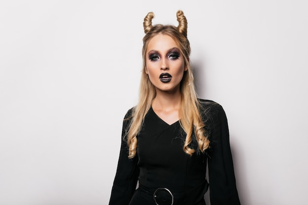 Retrato interior de mulher encaracolada de cabelos compridos, posando após o carnaval. garota vampira interessada em pé na parede branca.