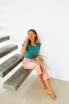 Retrato interior de mulher feliz comendo pizza com queijo, sentado na flor em casa moderna