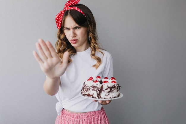 Retrato interior de mulher infeliz usa fita vermelha, posando com bolo. aniversariante segurando torta.