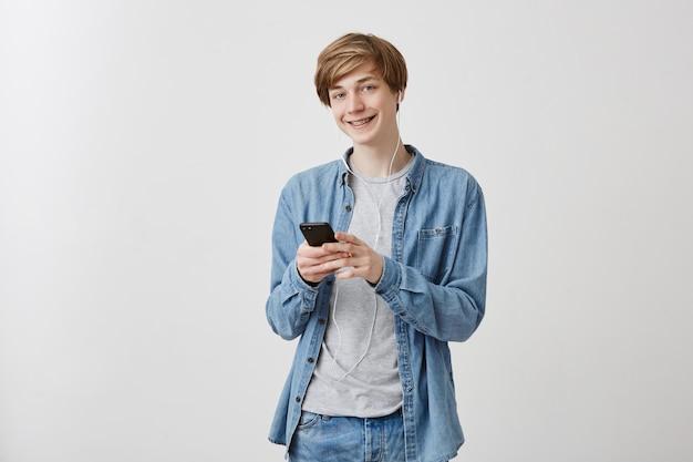 Retrato interior de um cara loiro europeu com olhos azuis em camisa jeans, segurando mensagens de celular com amigos contando histórias engraçadas, tem um sorriso agradável em pé