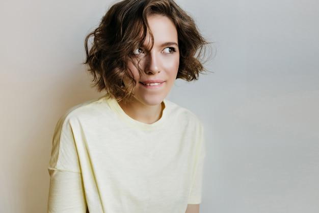 Retrato interior de uma garota engraçada em roupas brancas, olhando para longe. fascinante senhora de cabelo curto posando com expressão pensativa.