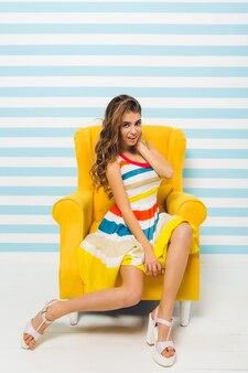 Retrato interior de uma garota incrível em trajes coloridos, descansando em uma poltrona amarela na parede listrada. bela jovem com cabelo comprido, usando um vestido bonito e sapatos de salto alto, relaxando em casa.