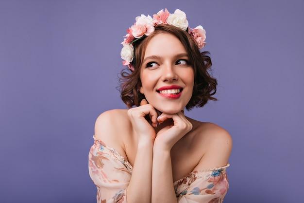 Retrato interior de uma garota romântica com rosas no cabelo curto. mulher adorável, sorrindo alegremente.
