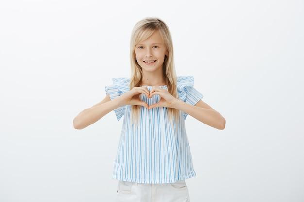 Retrato interior de uma jovem encantadora com cabelo loiro numa blusa azul, mostrando um gesto de coração sobre o peito e sorrindo de felicidade sobre a parede cinza