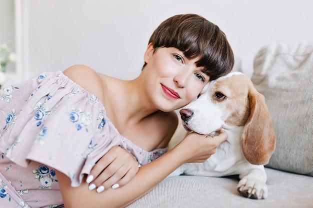 Retrato interior de uma jovem romântica com um penteado curto da moda posando tocando cachorrinho beagle e sorrindo