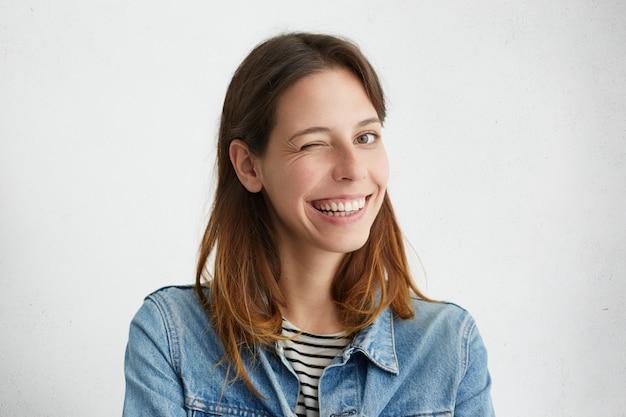Retrato interior de uma linda garota vestida com jaqueta jeans por cima listrado, sorrindo amplamente e piscando misteriosamente, tendo um olhar brincalhão.
