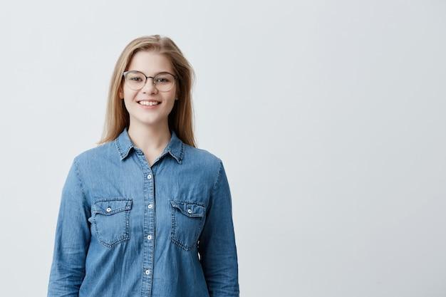 Retrato interior de uma linda jovem europeia loira com cabelos lisos, usando óculos elegantes, sorrindo, mostrando os dentes brancos para a câmera, sentindo-se feliz e despreocupada em seu primeiro dia de folga