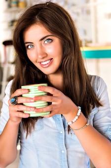 Retrato interior do estilo de vida de uma jovem morena posando no refeitório da cidade, apreciando seu saboroso café quente da manhã