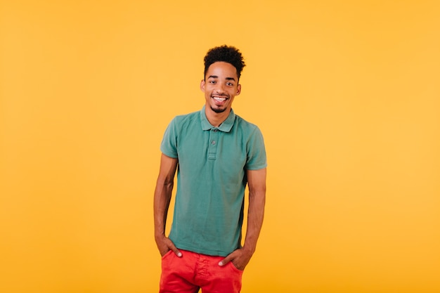 Retrato interior do homem negro sorridente em pé com as mãos nos bolsos. alegre cara africano isolado.