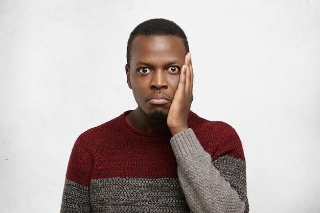 Retrato interior do jovem afro-americano esquecido engraçado de olhos esbugalhados, vestido de suéter casual, com um olhar confuso e sem noção, mantendo a mão na bochecha, esqueceu-se da importante reunião