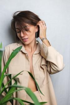 Retrato interior macio de mulher caucasiana gentil vestindo terno bege sem sutiã, posando atrás de planta tropical palm, cinza.