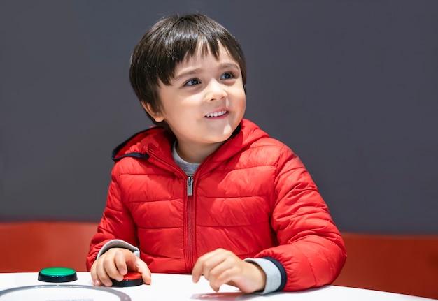 Retrato interno criança ativa se divertindo jogando no clube infantil da escola,