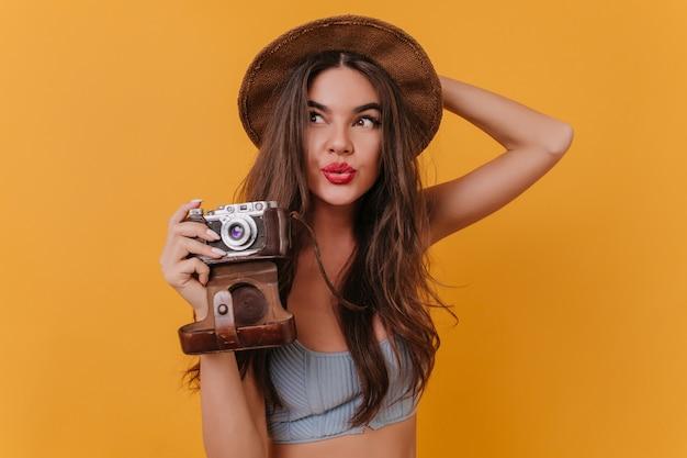 Retrato interno da encantadora garota de cabelos compridos segurando a câmera e olhando para longe