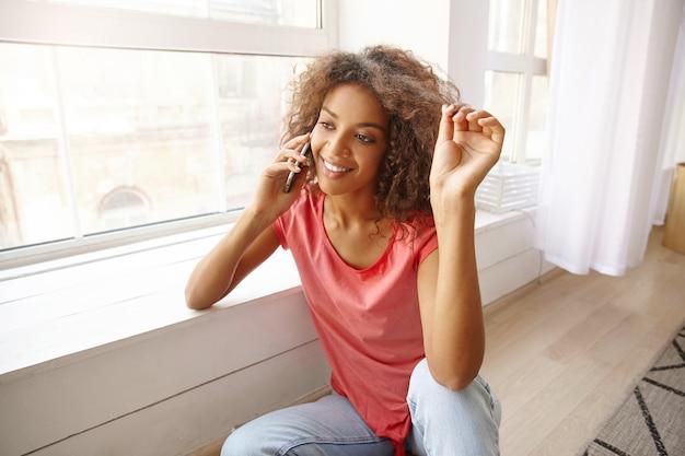 Retrato interno da encantadora jovem encaracolada puxando seu cabelo castanho e falando no celular, encostada no peitoril da janela e sorrindo alegremente