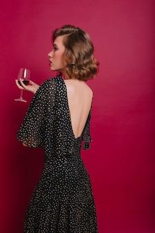 Retrato interno das costas de uma mulher séria em um vestido vintage olhando para longe e degustando vinho