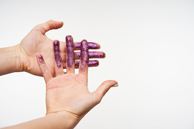Retrato interno das palmas das mãos de uma jovem senhora de pele clara sendo levantadas durante a demonstração de brilhos roxos, mantendo uma mão na outra enquanto posa em branco