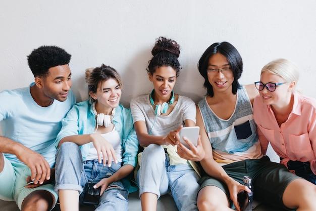 Retrato interno de alunos alegres segurando seus telefones e sorrindo. graciosa garota africana em fones de ouvido e jeans, fazendo selfie com amigos na universidade.