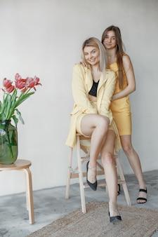 Retrato interno de duas irmãs se divertindo na sessão de fotos.