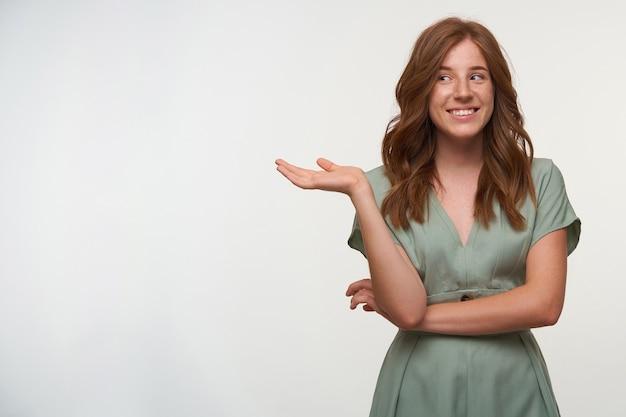 Retrato interno de feliz adorável jovem com cabeça de leitura feminina olhando para o lado com um sorriso encantador, apontando para longe com a palma da mão levantada, posando