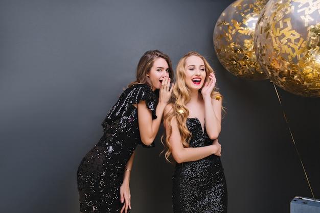 Retrato interno de garotas glamourosas, compartilhando rumores durante a festa. senhoras deslumbrantes em vestidos pretos falando sobre segredos enquanto celebram algo com balões.