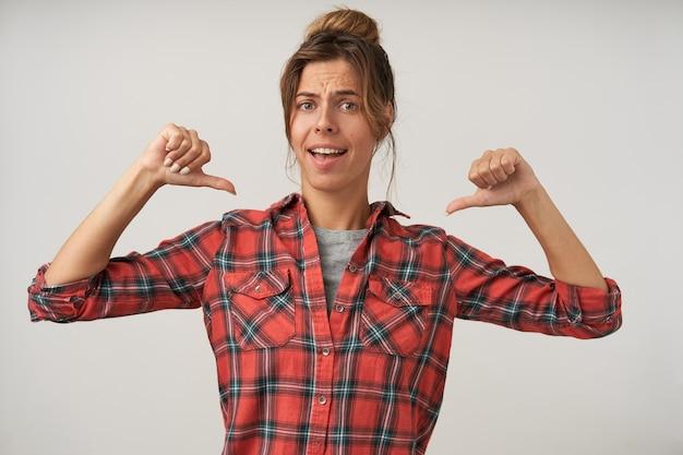 Retrato interno de jovem autoconfiante com cabelo escuro, posando em branco com roupas casuais, mostrando-se com os polegares